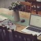 laptop on top of table beside vase of flowers